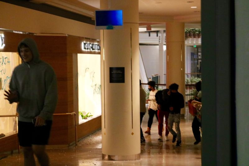 PMG PHOTO: ZANE SPARLING - People walk around inside Pioneer Place Mall during a night of rioting and looting on May 29 in Portland.
