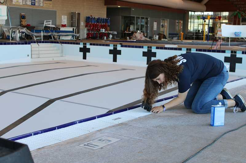 TERESA JACKSON/MADRAS PIONEER - Aquatics assistant Payton Kryla cleans at the Madras Aquatic Center Monday, June 29. Staff has clenaed tiles and is planning to seal them this week, among many projects.