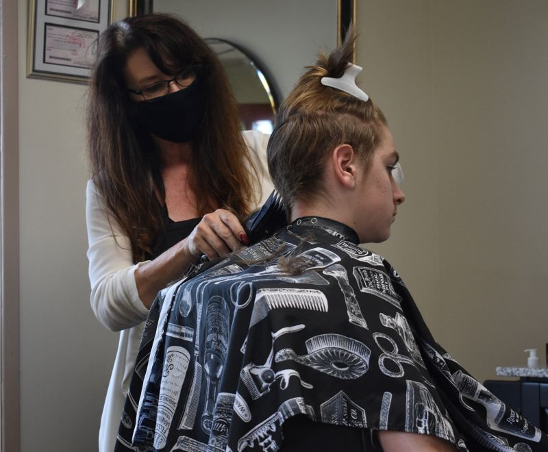 PMG PHOTO: TERESA CARSON - Donna Landers gives a young man a cool summer cut at the Troutdale Barber Shop on its first day back in business in three months.