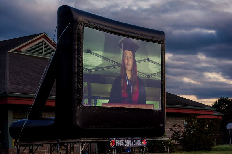 COURTESY PHOTOS: KAREN HAWLEY - Corbett School District set up a big screen so folks all over the parking lot could see the action on the stage. Here Valedictorian Sydney Smith is giving her speech.