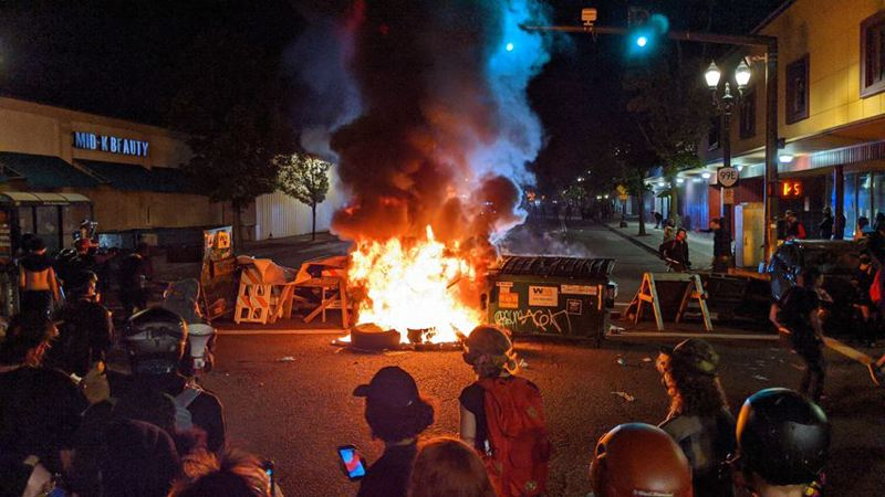 COURTESY PHOTO: JAMES MARTIN AND KOIN 6 NEWS - Protesters gather around a fire set overnight.