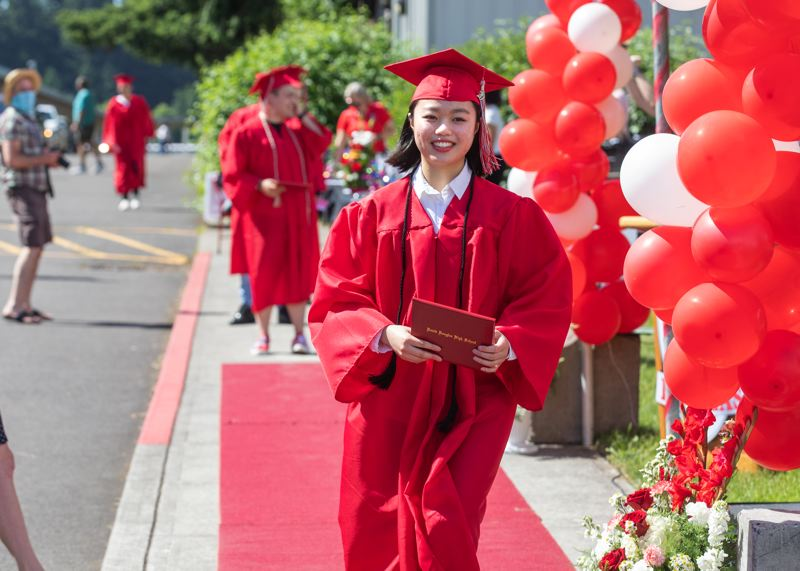 PMG PHOTO: JONATHAN HOUSE - TriQuang Nguyen marches forwards with her David Douglas diploma.