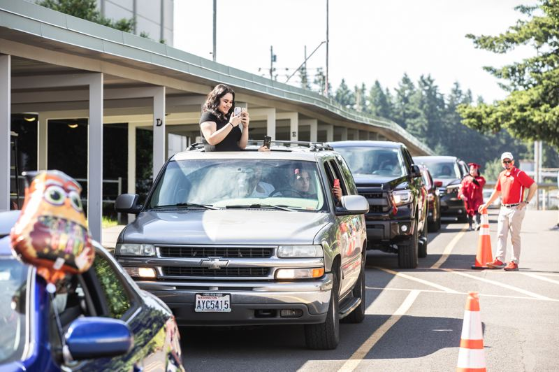 PMG PHOTO: JONATHAN HOUSE - Friends and family line up in cars to see their David Douglas students graduate.