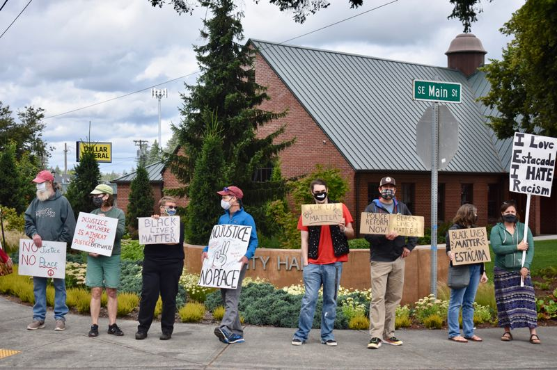PMG PHOTO: EMILY LINDSTRAND - Demonstrators hold signs in support of justice and peace, and against racism, in front of Estacada city Hall on Saturday, June 27.