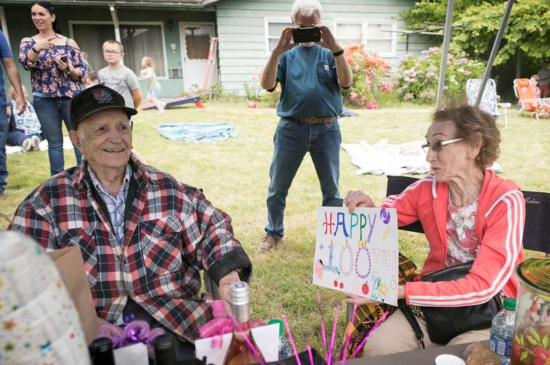 PMG PHOTO: JAIME VALDEZ - Mary Stobbe holds up one of the many cards Paul Herberholz, left, received during a drive-by parade held in his honor on Saturday afternoon.