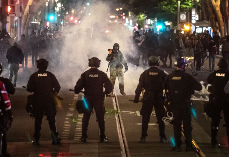PMG PHOTO: JONATHAN HOUSE - Police face off against protesters in downtwon Portland on June 7.