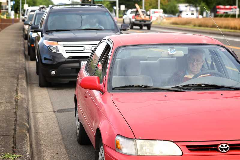 PMG PHOTO: JAIME VALDEZ - Portland resident John Hively reads a book while waiting for DEQ testing in a line of cars along Tualatin-Sherwood Road.