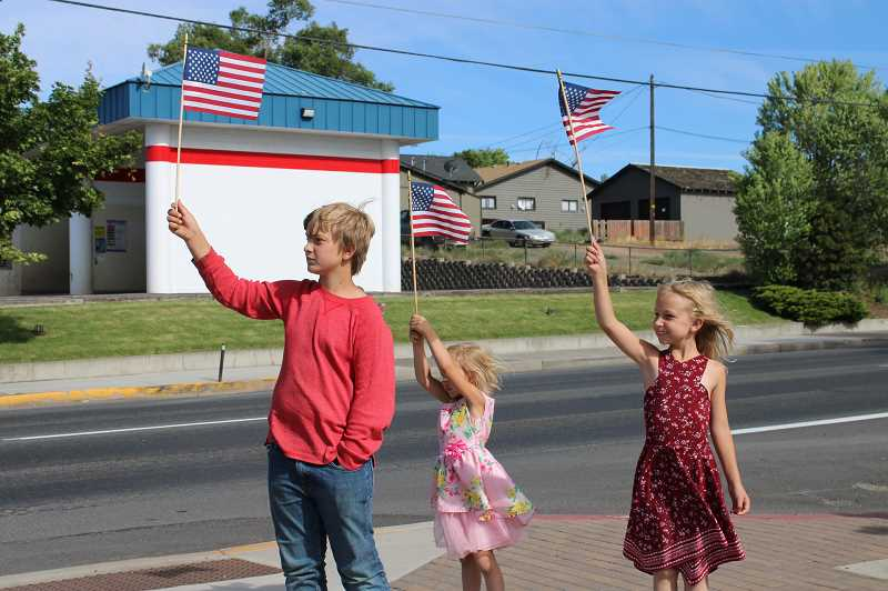 TERESA JACKSON/MADRAS PIONEER - Riley, 11, Zoey, 4, and Grace Baxter, 7, hold flags up to welcome veteran motorcycle riders to Madras.