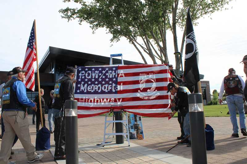 TERESA JACKSON/MADRAS PIONEER - The sign that will be installed on Highway 26 shows through the flag that is about to be lowered to display the sign at a ceremony at the memorial plaza by Madras City Hall on June 27.