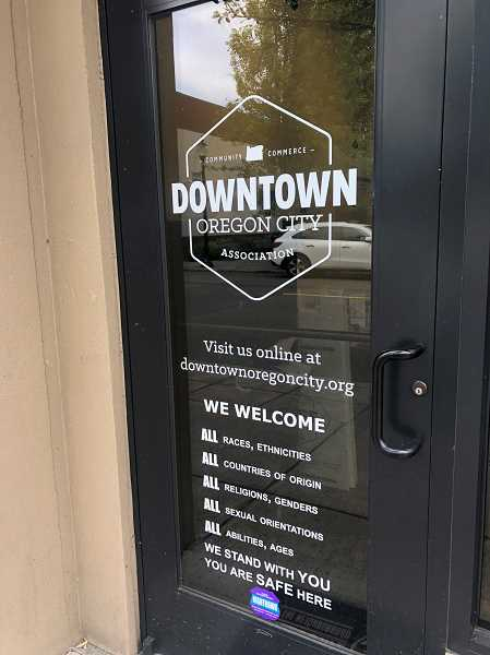 A sign of the door of the Downtown Oregon City Association signals the organization's longtime formal equality and solidarity stance.