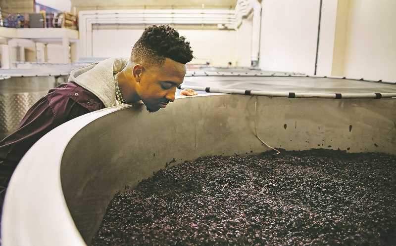 COURTESY PHOTO - CJ McCollumn checks out a tank of pinot noir grapes at Adelsheim Vineyvard in Newberg.