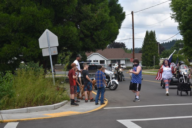 PMG PHOTO: EMILY LINDSTRAND - A participant in the Estacada Patriotic March shares candy with those watching the event.