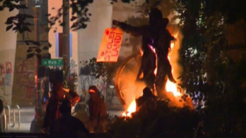 COURTESY PHOTO: KOIN 6 NEWS - Protesters set fire to the Pioneer Family statue near the downtown Justice Center.