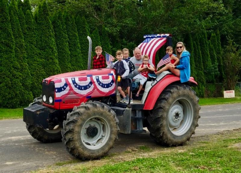 COURTESY PHOTO: KATHY OBRIST - Families cruised along Jackson Road in their tractors to celebrate the Fourth of July.