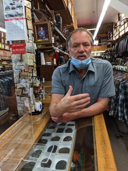 PMG: JOSEPH GALLIVAN - Portland Outdoor Store owner operator Brad Popick lowers his mask momentarily as he explains how the company is surviving on lowered sales. The western workwear store celebrates 100 years this year and has a loyal customer base, althought it has little online presence.