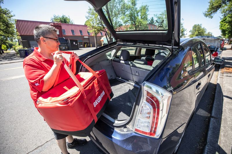 PMG PHOTO: JAIME VALDEZ - Grubhub delivery driver Boni Melchor loaded her vehicle last year. Portland's City Council could limit the amount food delivery services like Grubhub and DoorDash could charge restaurants.