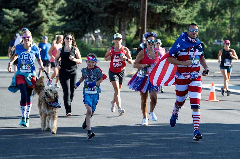 LON AUSTIN - Patriotic running gear, including flag capes and skirts, marks the annual John Marsh Run Saturday, kicking off the Fourth of July morning. A total of 48 runners took part in the 5K race, which featured social distancing rules at the start. The Marsh Run was the only element of the annual Splash 'N Dash activities that was carried out live Saturday, with the other elements to go vurtual this year, James Blanchard, below right, was the overall winner. Blanchard smoked the course to finish in 19:33.7. Chuck Coats, left, was just behind, finishing in an even 20:00.92. Beth Cokenow was the top female finisher, clocking a 24:52.6.