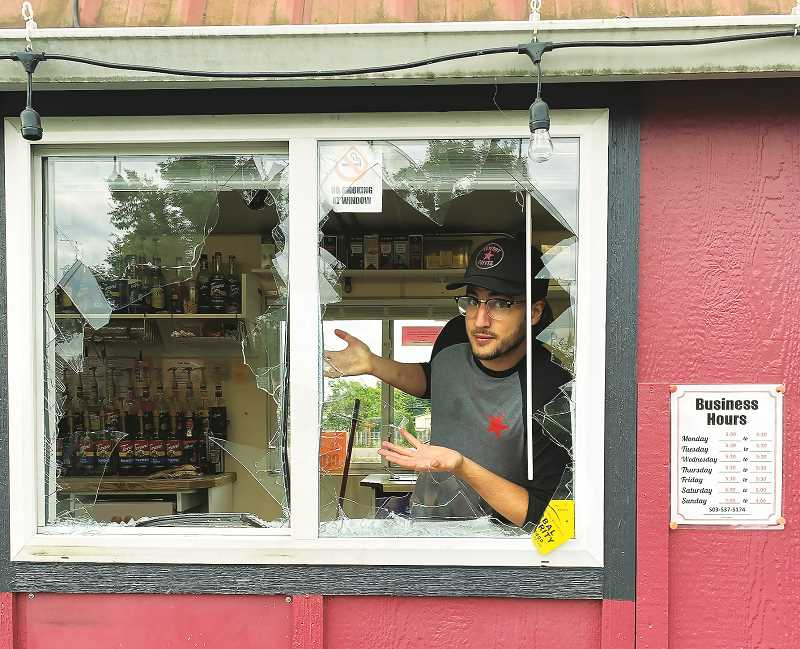 COURTESY PHOTO - Coffee Barn co-owner Drew Delbridge shows the damage the Everest Road business sustained at the hands of a vandal on July 5.
