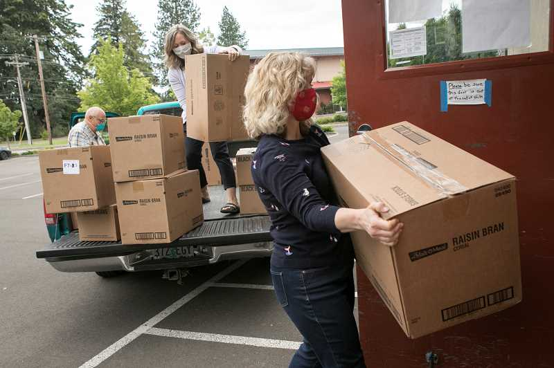PMG PHOTO: JAIME VALDEZ - Tiffany Mitton, right, Kiersten Homer, middle, and Ken Stevens, all members of Church of Jesus Christ of Latter-day Saints in the Sherwood, Tualatin, Tigard area, unload boxes of food to the St. Vincent de Paul Food Pantry in Tigard.