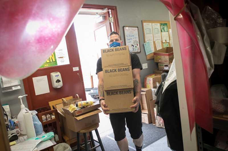 PMG PHOTO: JAIME VALDEZ - John Judkins, a member of the Church of Jesus Christ of Latter-day Saints in Tigard, carries boxes of black beans inside the St. Vincent de Paul Food Pantry in Tigard.