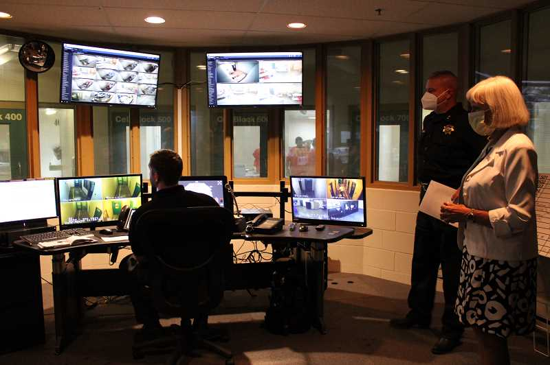 TERESA JACKSON/MADRAS PIONEER - County Commissioner Mae Huston, far right, and Sheriff Jim Adkins take a look at the control panel where sheriff's deputies monitor inmates via video at the Jefferson County Correctional Facility on July 1.