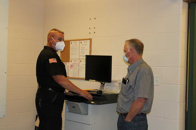 TERESA JACKSON/MADRAS PIONEER - Sheriff Jim Adkins shows Commissioner Wayne Fording the intake area at the Jefferson County Correctional Facility during the board's annual inspection July 1.