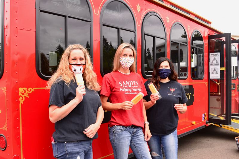 PMG PHOTO: BRITTANY ALLEN - Khrys Jones, Crystal Bacon and Machel Heldstab prepare to board the trolley with popsicles for all.