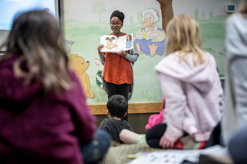 REVIEW PHOTO: JONATHAN HOUSE - Intel engineer Dr. Arlyne Simon reads from her book 'Abby Invents Unbreakable Crayons' during Multicultural Children's Book Day at the Lake Oswego Public Library.