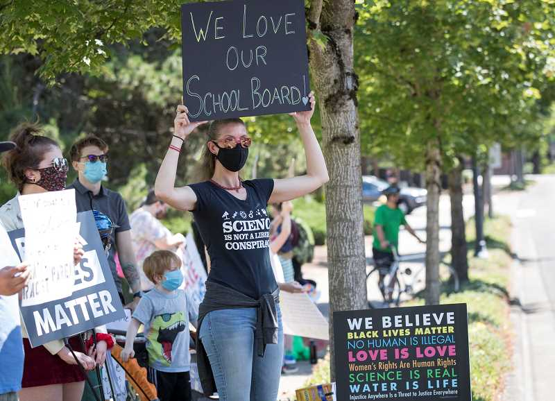 PMG PHOTO: JAIME VALDEZ -  A woman holds a sign showing support for the Sherwood School Board during a Black Kids Matter Unity Event, which faced off with an All Kids Matter rally across the street that was sponsored by Oregonians for Trump.