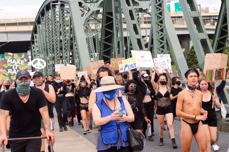 PMG PHOTO: ZANE SPARLING - PDX Stripper Strike activists march along the Hawthorne Bridge on Saturday, July 11.