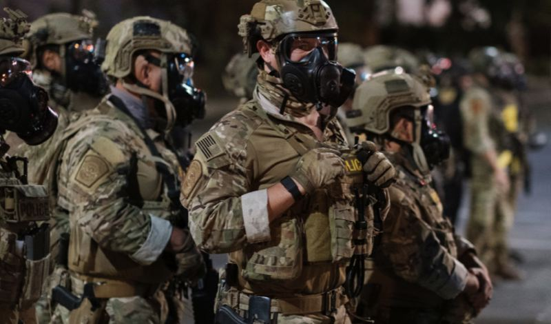 COURTESY PHOTO: KOIN 6 NEWS - Law enforcement agents, rigged for tear gas deployment, stand on the streets of downtown Portland early Wednesday, July 15.