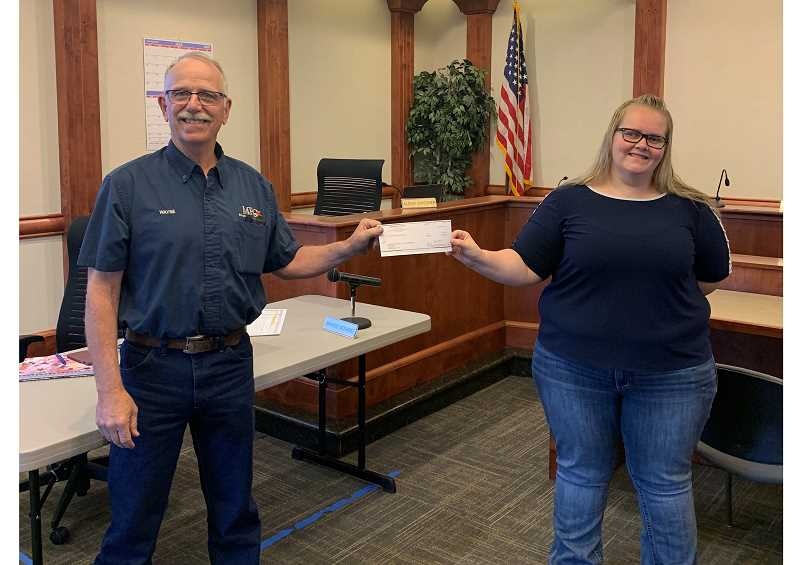 COURTESY PHOTO - Jefferson County Commissioner Wayne Fording hands  a $30,000 check to Caren Pilkington, Kids Club's director at a special meeting of the commissioners Friday, July 10.