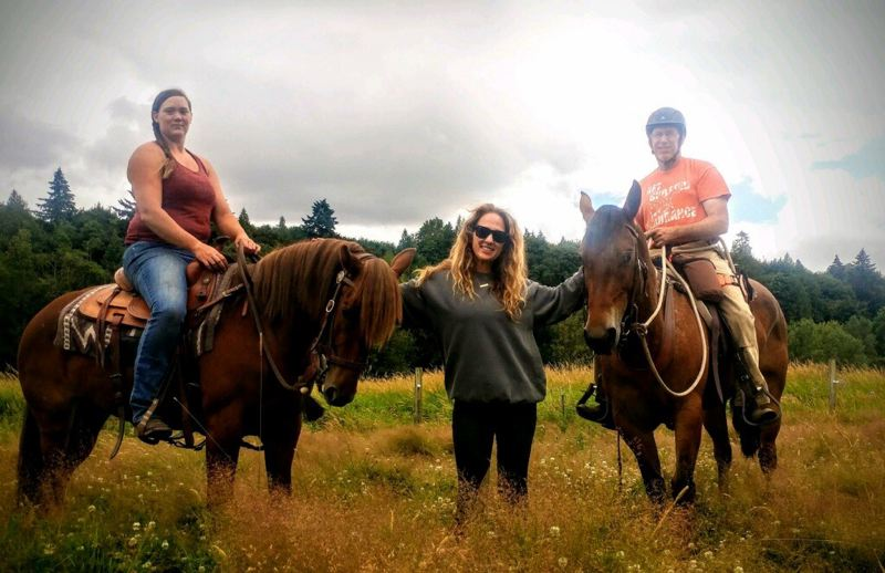 COURTESY PHOTO - Trainer Heather Longshore (left), Flawless Aesthetics owner Trish Waters (middle) and trainer Peter Halay post for a photo with two mustangs that will be put up for adoption in September, Zena and Greta.