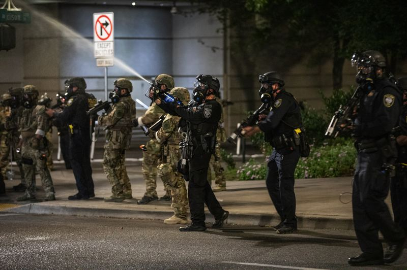 PMG PHOTO: JONATHAN HOUSE - A federal police officer sends a plume of pepper spray into a crowd of protesters during a demonstration in downtown Portland on Friday, July 17.