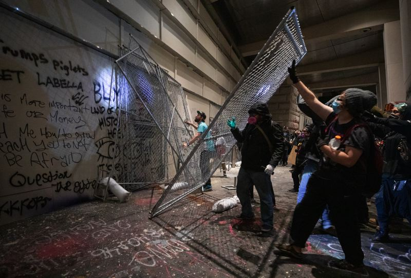 PMG PHOTO: JONATHAN HOUSE - Protesters pushed chain-link fence barricades across the doors of the already-reinforced doors of the federal courthouse in downtown Portland on Friday, July 17.