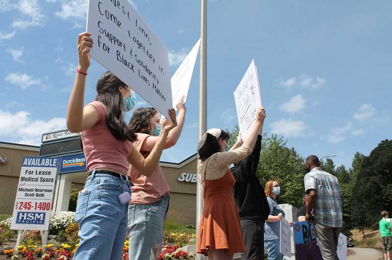 PMG PHOTO: HOLLY BARTHOLOMEW - West Linn students demonstrated on the corner of 10th Street and Blankenship Road near the I-205 on-ramp Friday, July 17.