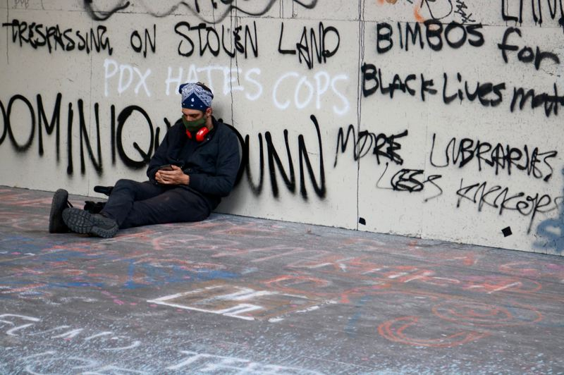 PMG PHOTO: ZANE SPARLING - A protester leans against the graffiti'd wall of the federal courthouse in downtown Portland on Friday, July 17.