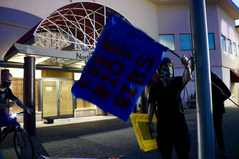 PMG PHOTO: ZANE SPARLING - A protester waves a flag reading 'Free Riot Ribs,' a local mutual-aid group supporting demonstrators, outside the North Precinct police building on Saturday, July 18 in Portland.