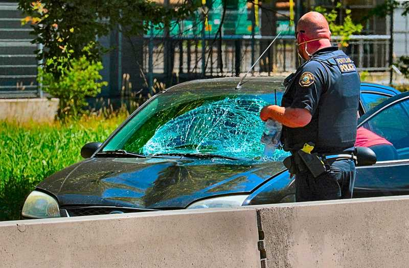 DAVID F. ASHTON - A Central Precinct officer examined the damaged northbound car which struck a pedestrian who was crossing S.E. McLoughlin Boulevard - by clambering over the high median Jersey Barrier near the Bybee Bridge.