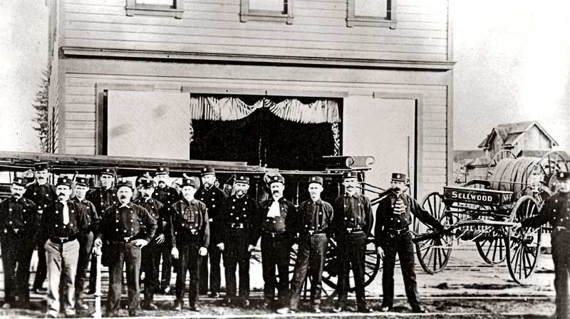 COURTESY OF SMILE HISTORY COMMITTEE - These serious-looking gentlemen, with their tight shirts and ties, were volunteers of the Sellwood Fire House. The independent City of Sellwood had no extra money to provide horses for their ladder and hose truck, sohardy young men like these were recruited from the neighborhood to haul the wagons by hand, and muscle them through the dirt streets of Sellwood, to put out fires.