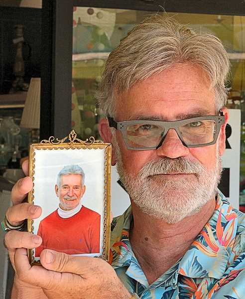 DAVID F. ASHTON - Brent Heeb, of Stars Antiques Malls in Westmoreland, holds a photo of his late partner, Darwin Otto.