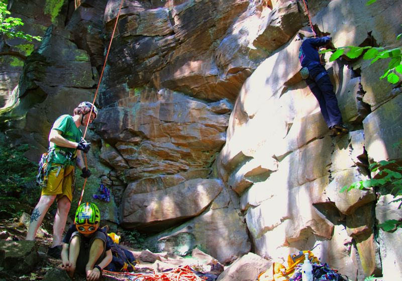 PMG PHOTO: SAM STITES - Paul Losch (left), Jasper Losche (bottom) and Tom Saddoris (right) climb the crag at Madrone Wall Park in Clackamas County on Monday, July 20, following the park's reopening marked by the fledging of three peregrine falcons.