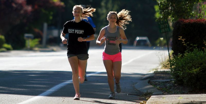 PMG PHOTO: MILES VANCE - St. Helens fall athletes got in on the act, too, with members of its girls cross country team (including Alydia Smith, left, and Ellyzabeth Wilson) stepping out for a morning run on Tuesday, July 21.