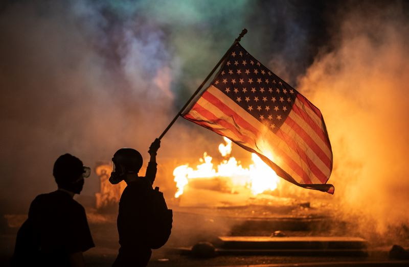 PMG PHOTO: JONATHAN HOUSE - Portland Tribune photographer Jonathan House was shot with an impact munition by federal officers while filming a demonstrator waving an American flag just after midnight on July 21.