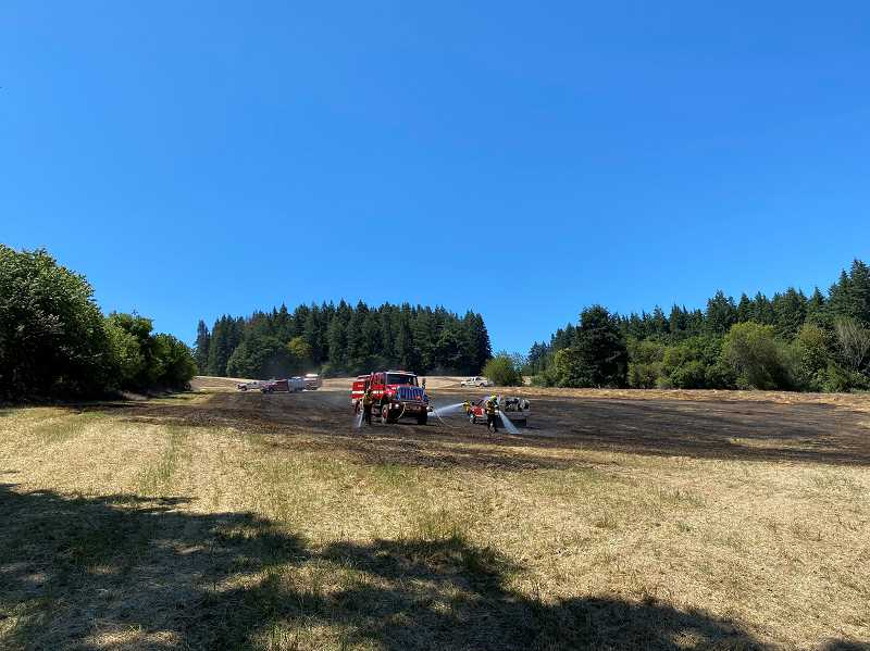 COURTESY PHOTO - Gaston firefighters put water on a field fire north of Gaston Monday, July 20. It was the first of two fires started by the same combine on consecutive days.