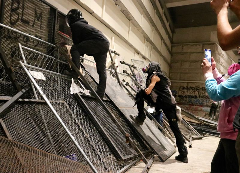 PMG PHOTO: ZANE SPARLING - Protesters scramble up makeshift barricades at the federal courthouse in downtown Portland on Saturday, July 18.