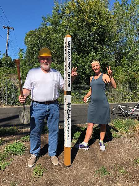 COURTESY ROTARY CLUB OF TIGARD - Marland Henderson, a Rotarian and former Tigard City Council member, and Cheron Calder, past president of Tigard Rotary Club, stand behind a Peace Pole recently installed at Tigard and Main streets, along the Tigard Heritage Trail.