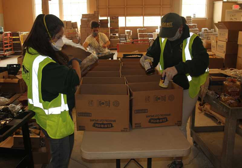PMG PHOTO: JUSTIN MUCH - Woodburn CERT volunteers help fill boxes at AWARE Food Bank in April. AWARE is among the recent recipients of Maps Community Foundation's helping hand project.