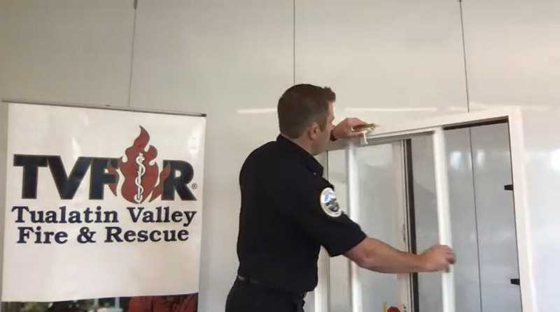PMG PHOTO - Tualatin Valley Fire & Rescue public affairs officer, Stefan L. Myers, demonstrates the use of a window stopper. The device only opens the window four inches to help children from falling out of an apartment or home.