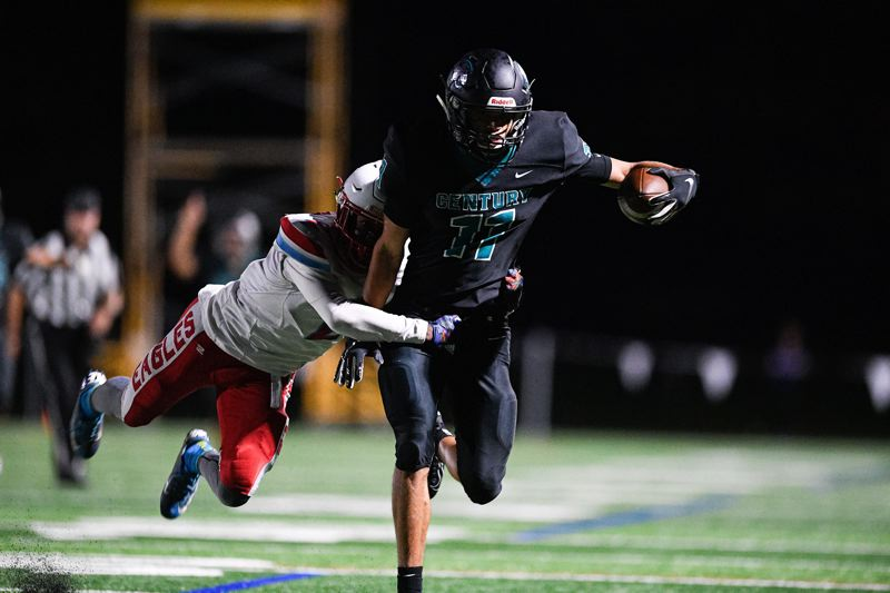 PMG PHOTO: CHRISTOPHER OERTELL - Century's Chance Sparks drags a Centennial defender following a catch during the Jaguars' game against the Eagles Sept. 27, 2019, at Century High School.